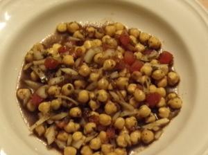 Kichererbsensalat im Teller mit Tomate und Zwiebel